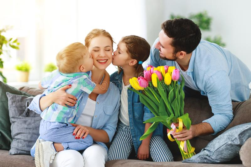 Happy mother`s day! father and children congratulate mother on holiday. And give flowers royalty free stock photography