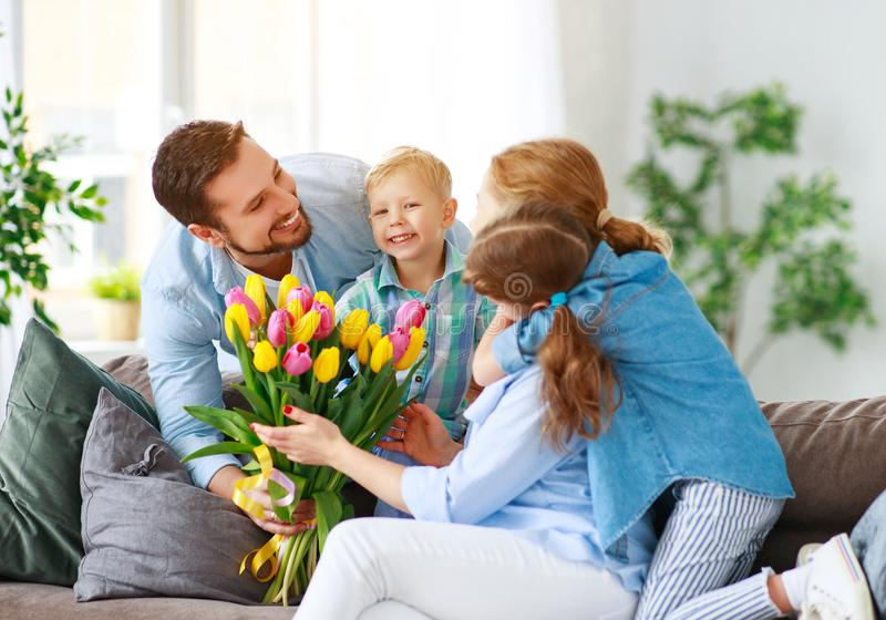 Happy mother`s day! father and children congratulate mother on holiday. And give flowers stock image