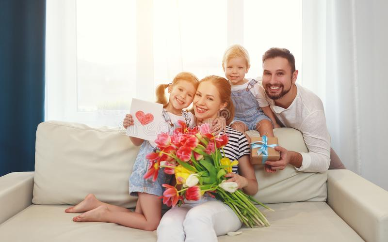 Happy mother`s day! father and children congratulate mother on h. Oliday and give flowers royalty free stock photo