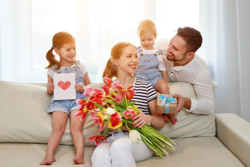 Happy mother`s day! father and children congratulate mother on h stock photography