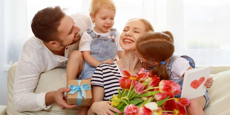 Happy mother`s day! father and children congratulate mother on h stock photo