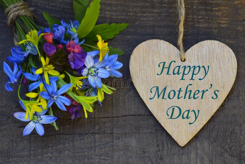 Happy Mother`s Day greeting card with spring flowers bouquet and decorative heart on old wooden background. royalty free stock photo