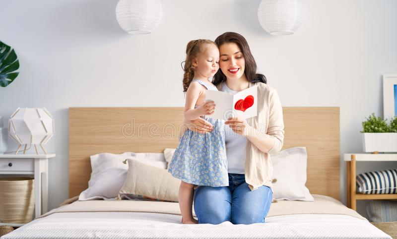 Happy mother`s day. ! Child daughter is congratulating mom and giving her postcard and gift. Mum and girl smiling and hugging. Family holiday and togetherness royalty free stock image