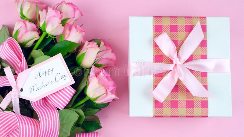 Mother`s Day overhead with roses and gift on pink wood table. royalty free stock images