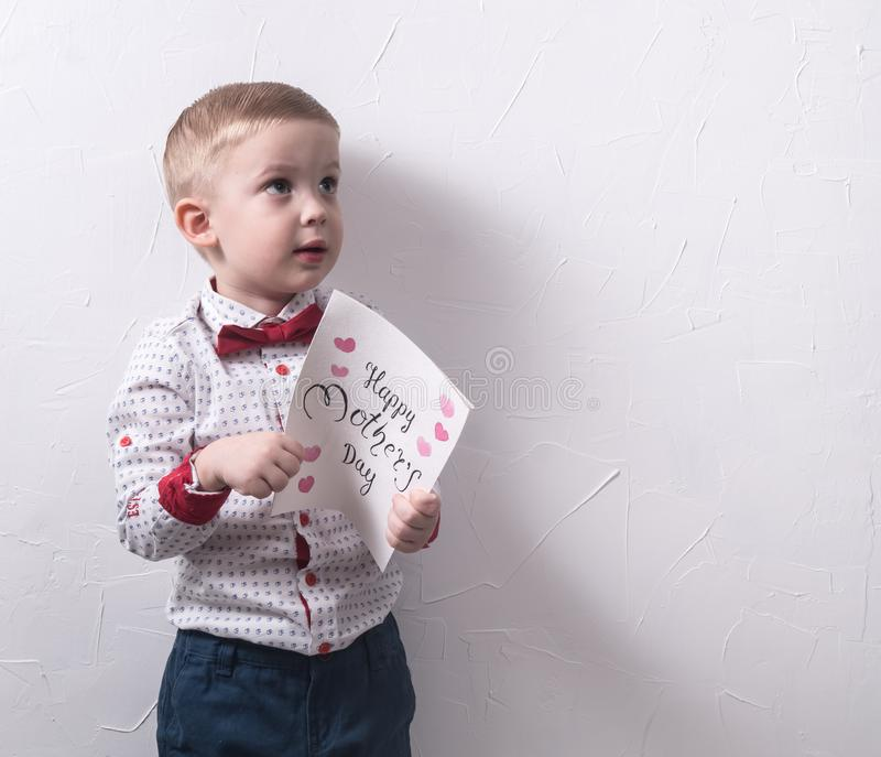 Happy mother& x27;s day: a small timid boy in a shirt and trousers with a greeting card. stock images