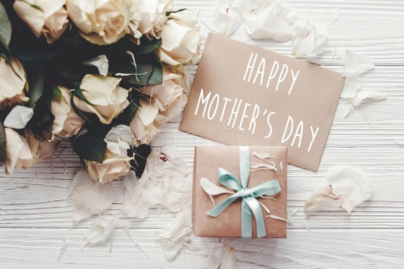 Happy Mother`s Day text sign on craft greeting card and white roses bouquet, gift box on wooden background, flat lay. Mothers day. Floral greeting card royalty free stock image