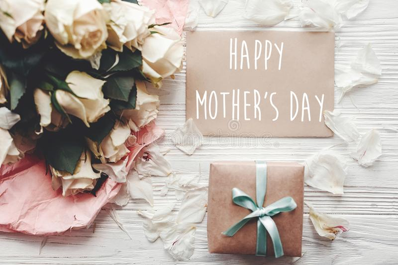 Happy Mother`s Day text sign on craft greeting card and white roses bouquet, gift box on wooden background, flat lay. Mothers day. Floral greeting card stock photo