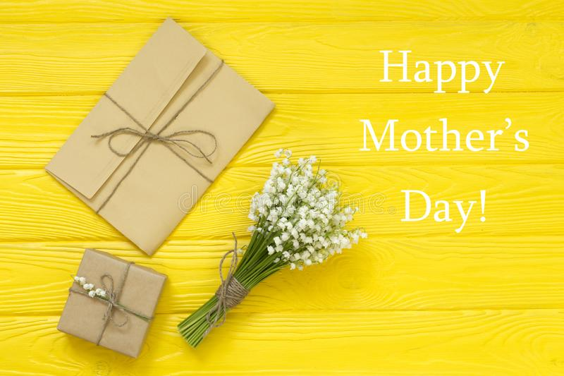 Happy Mother`s day text on yellow rustic wooden background. greeting card and gift box concept spring flowers flat lay royalty free stock photography