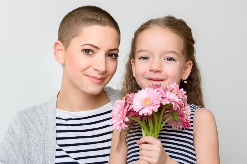 Happy Mother`s Day, Women`s day or Birthday background. Cute little girl giving mom, cancer survivor, bouquet of pink daisies. stock photography