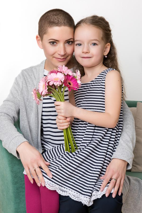 Happy Mother`s Day, Women`s day or Birthday background. Cute little girl giving mom, cancer survivor, bouquet of flowers. Happy Mother`s Day, Women`s day or stock photo