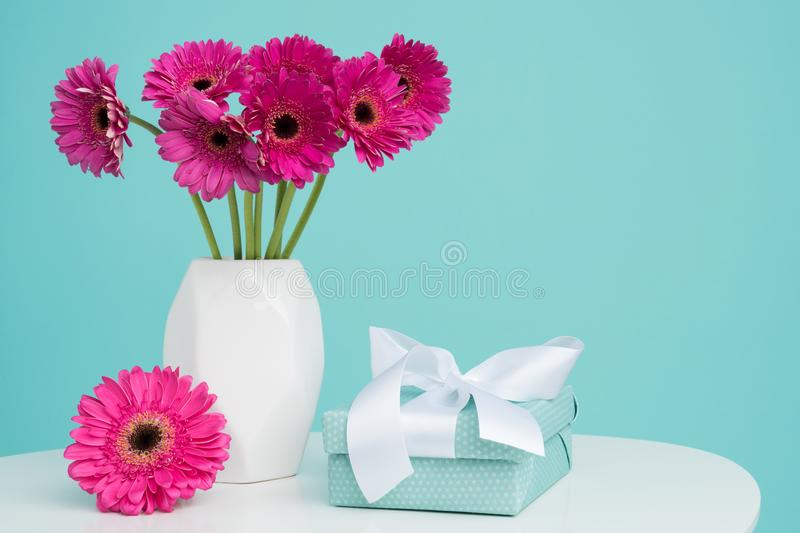 Dark pink gerberas in a vase on a retro table. Happy Mother`s Day, Women`s Day, Valentine`s Day or Birthday background. Happy Mother`s Day, Women`s Day royalty free stock image