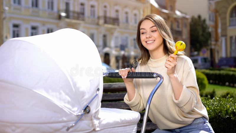Happy mother showing rattle toy to newborn in baby carriage, walk in park royalty free stock images