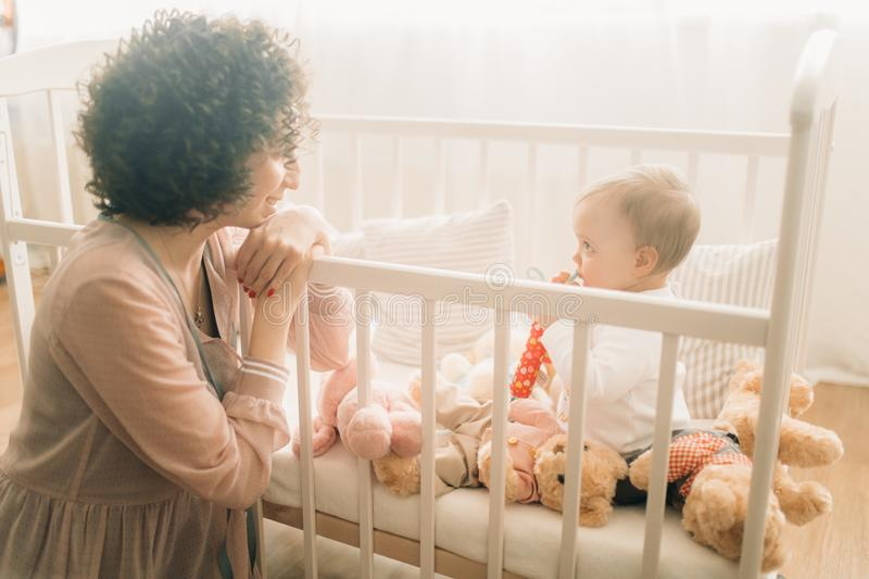 Happy mother sits next her baby in the crib royalty free stock images