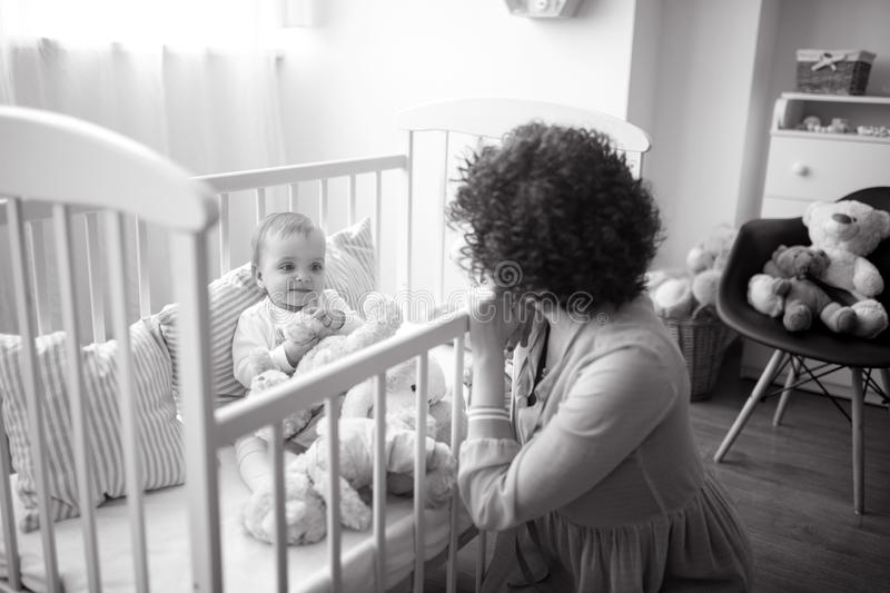 Happy mother sits next her baby in the crib. Happy mother sits next her baby with toys in the crib. Black and white image stock photo