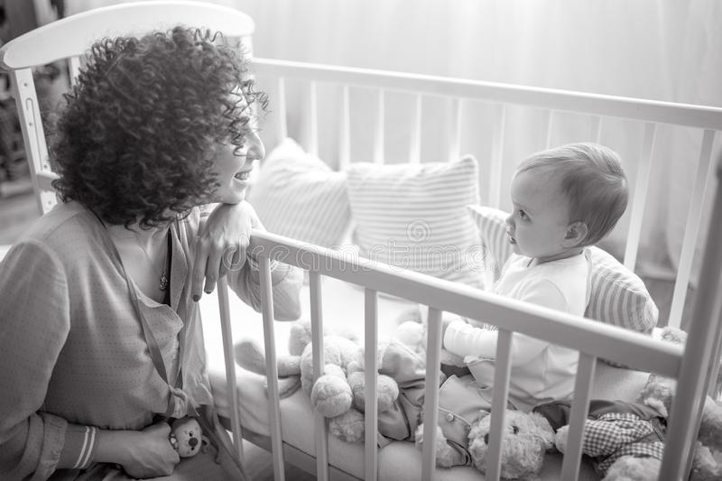 Happy mother sits next her baby in the crib. Happy mother sits next her baby with toys in the crib. Black and white image royalty free stock photography