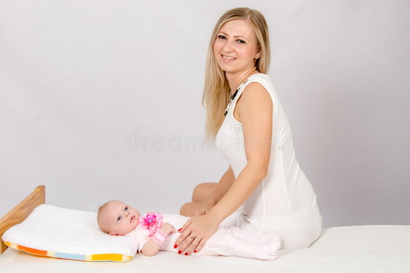 Happy mother sitting on a bed at his two-month daughter and looks in the picture. A two-month baby lying on his back on the bed, sitting next to the child and royalty free stock images