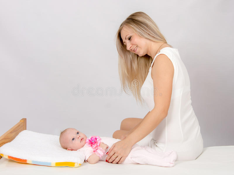 Happy mother sitting on a bed and looking at a two-month daughter. A two-month baby lying on his back on the bed, sitting next to the child and mother looking at stock photos