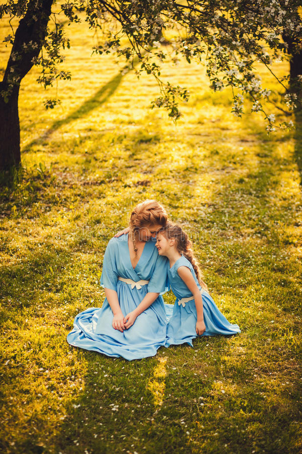 Happy mother sitting little girl on grass. Happy mother sitting little girl sitting on grass in sunlight. outdoor shot royalty free stock photography