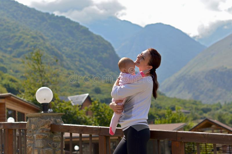 Happy mother with a small child standing on the terrace of a country house surrounded by mountains royalty free stock photos