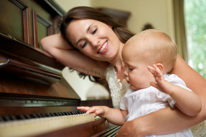 Happy mother smiling as baby plays piano stock photos