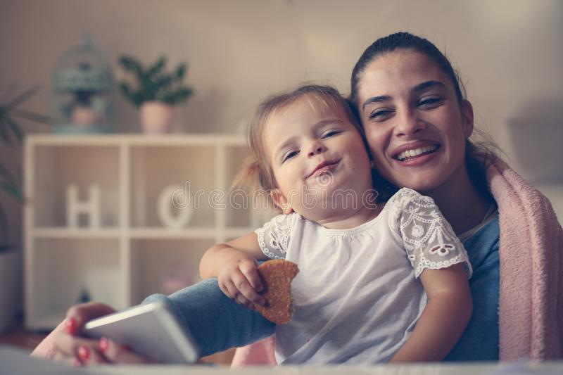 Mother and smiling girl taking self picture at home. Happy mother and smiling girl taking self picture at home stock photos