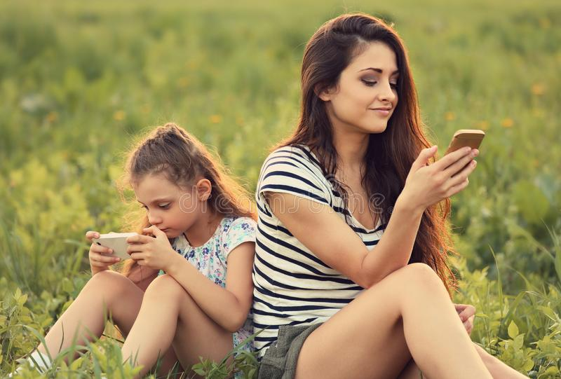 Happy mother and smiling kid girl sitting on green glass and playing in mobile phone. Contemporary family lifestyle. Concept. Ton stock image