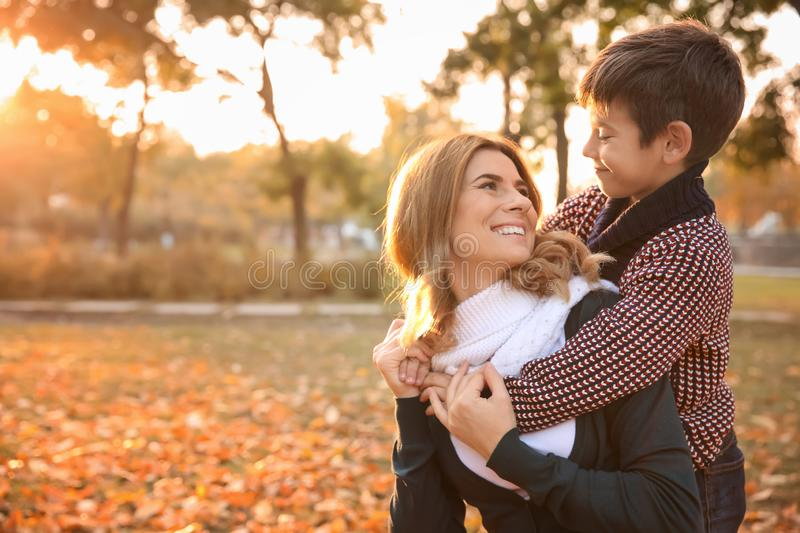 Happy mother and son in autumn park stock photography