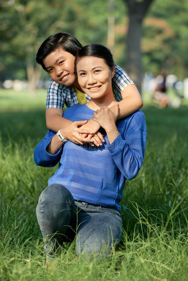 Happy mother and son. Cheertul Vietnamese teenage boy hugging his happy mother from behind royalty free stock photography