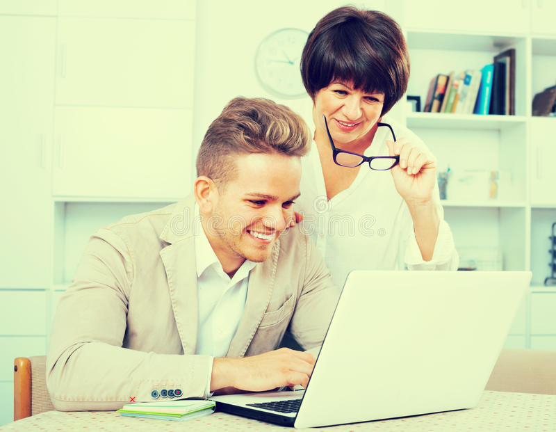 Happy mother and son consider software on laptop stock photos