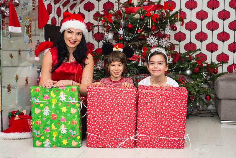 Happy mother with son and daughter. In front of Christmas tree having fun with presents royalty free stock photo