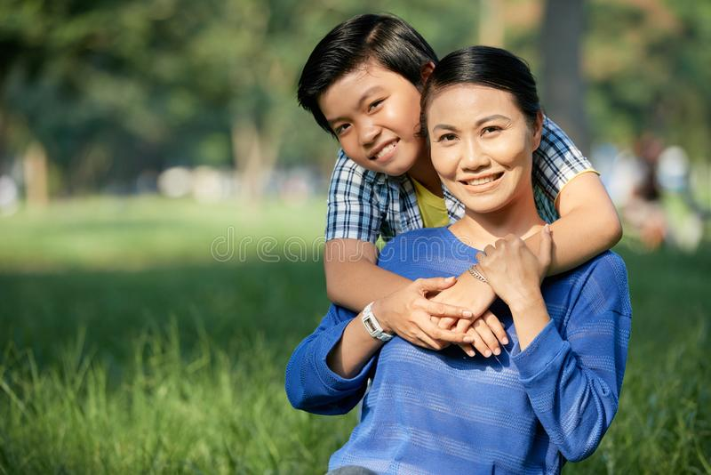 Happy mother and son. Joyful Vietnamese boy hugging his mother when they are spending weekend in park royalty free stock photos