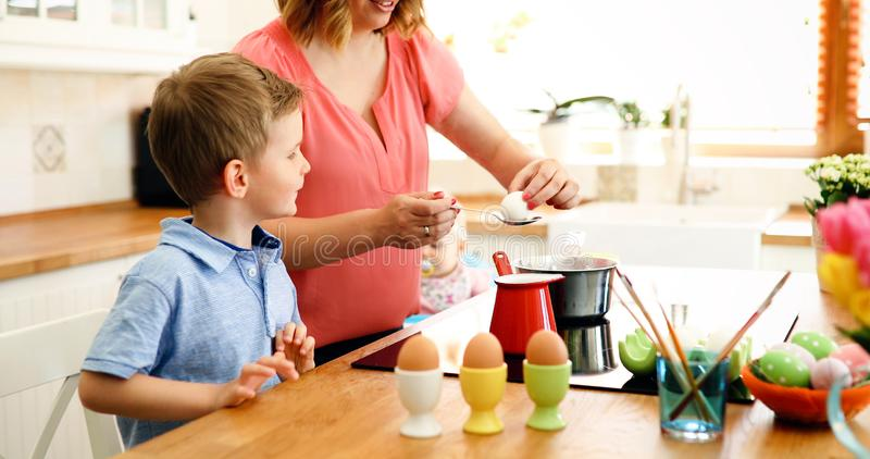 Mother and son paint Easter eggs stock photography