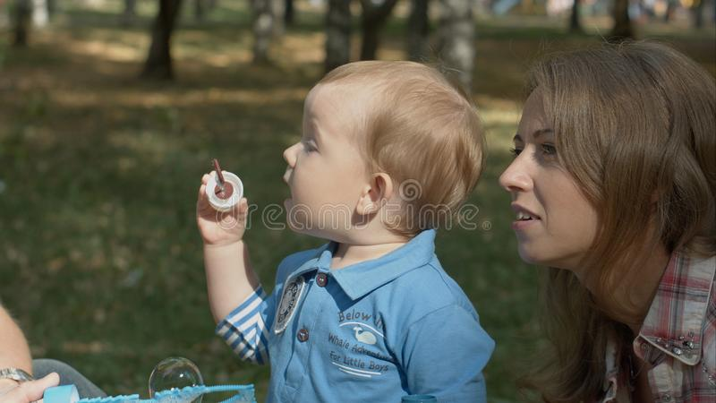 Happy mother and son in the park blowing soap bubbles outdoor portrait. royalty free stock image