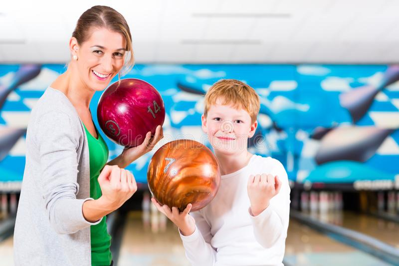 Mother and son playing together at bowling center. Happy mother and son playing together at bowling center royalty free stock photos