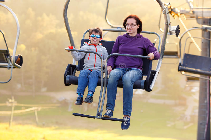 Happy mother and son ride chair lift. Happy mother and her little son ride chair lift in Sigulda, Latvia, Europe stock photos