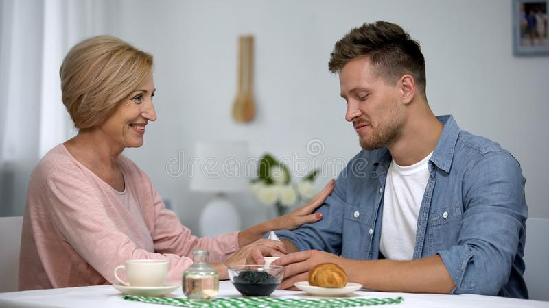Happy mother and son talking as having tea time, long-awaited meeting, care royalty free stock image