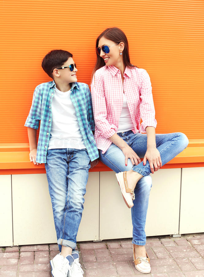 Happy mother and son teenager wearing a checkered shirt and sunglasses in city stock images