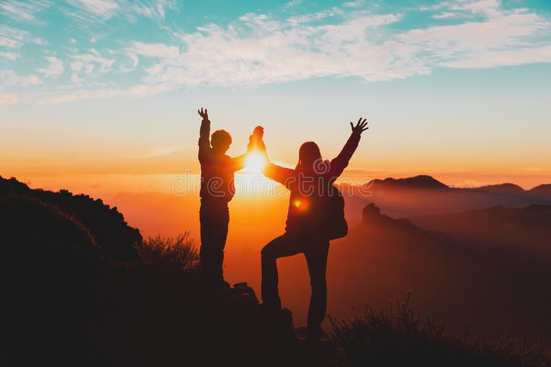 Happy mother and son travel in mountains at sunset stock image