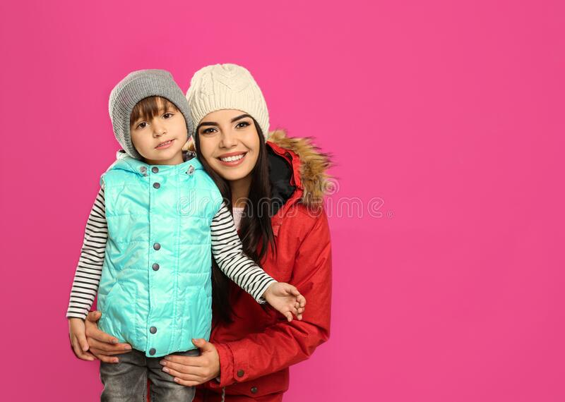 Happy mother and son in warm clothes on background, space for text. Winter vacation royalty free stock photos