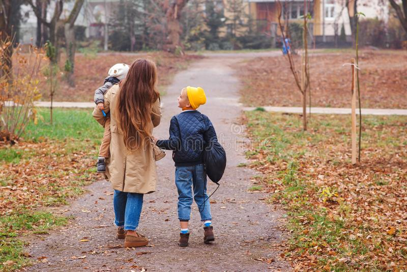 Happy mother and sons going to school and to kindergarten. Mother with two sons on walk in autumn. Back to school. Happy family in stock photo