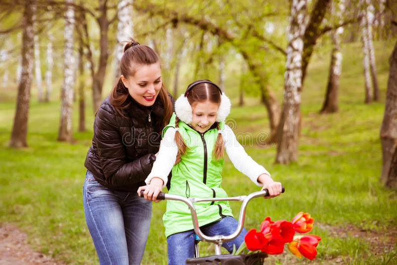 Happy mother teaches his daughter to ride a bike. Mother holds daughter from falling royalty free stock image