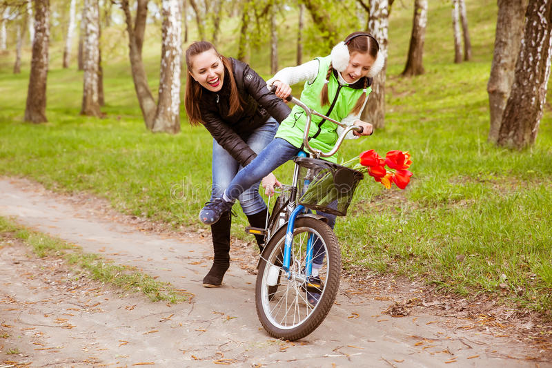 Happy mother teaches his daughter to ride a bike in the park. Mother holds daughter from falling stock photo