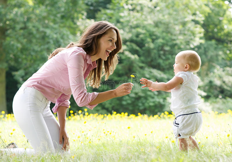 Happy mother teaching baby to walk in the park stock image