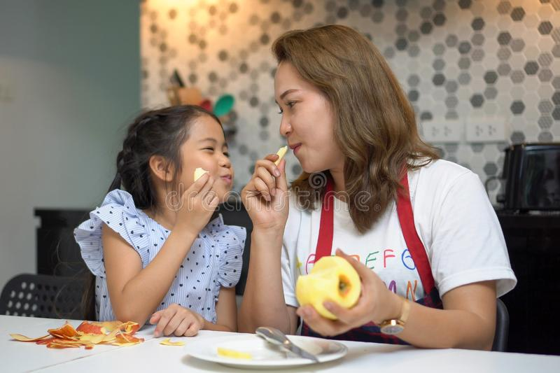 Happy Mother teaching daughter peeling and eating  red apples together on table in kitchen at home . loving family.  child girl. Excited looking Mom cooking stock photos