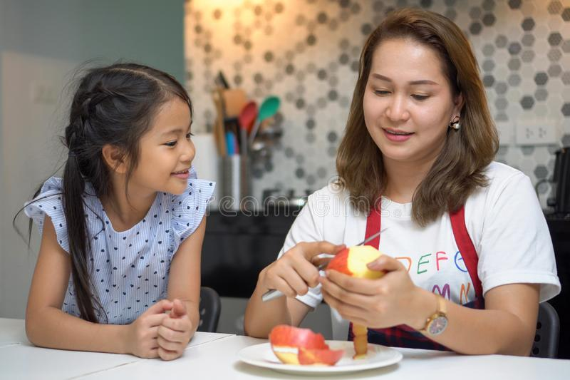 Happy Mother teaching daughter peeling red apples together on table in kitchen at home . loving family.  child girl excited. Looking Mom cooking indoors, kid stock photos