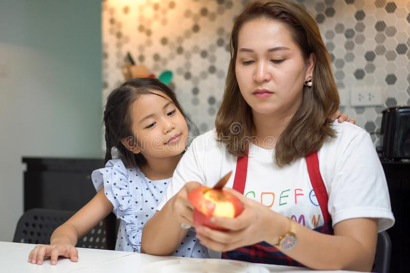 Happy Mother teaching daughter peeling red apples together on table in kitchen at home . loving family.  child girl excited. Looking Mom cooking indoors, kid stock image