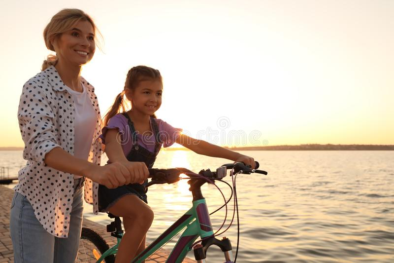 Happy mother teaching her daughter to ride bicycle near river. At sunset royalty free stock image