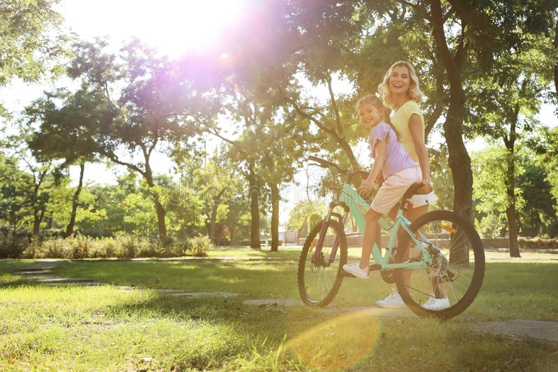 Happy mother teaching her daughter to ride  in park. Happy mother teaching her daughter to ride bicycle in park stock images