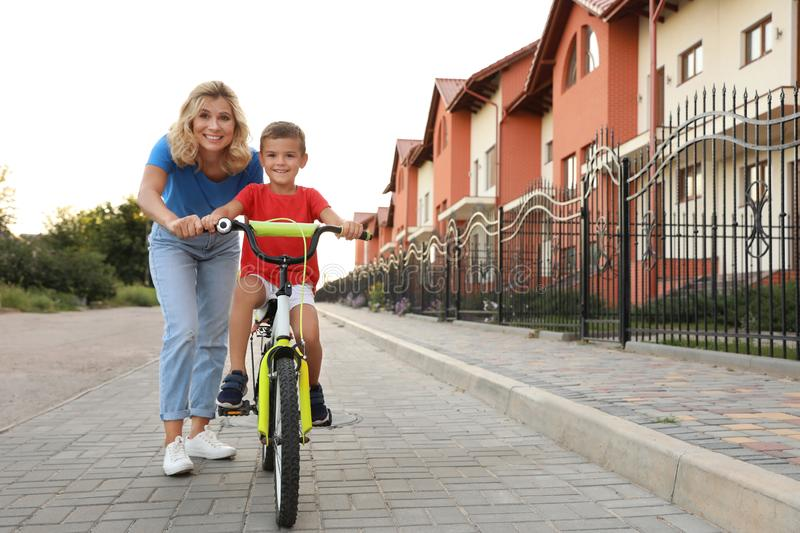 Happy mother teaching her son to  bicycle in city. Happy mother teaching her son to ride bicycle in city royalty free stock photos