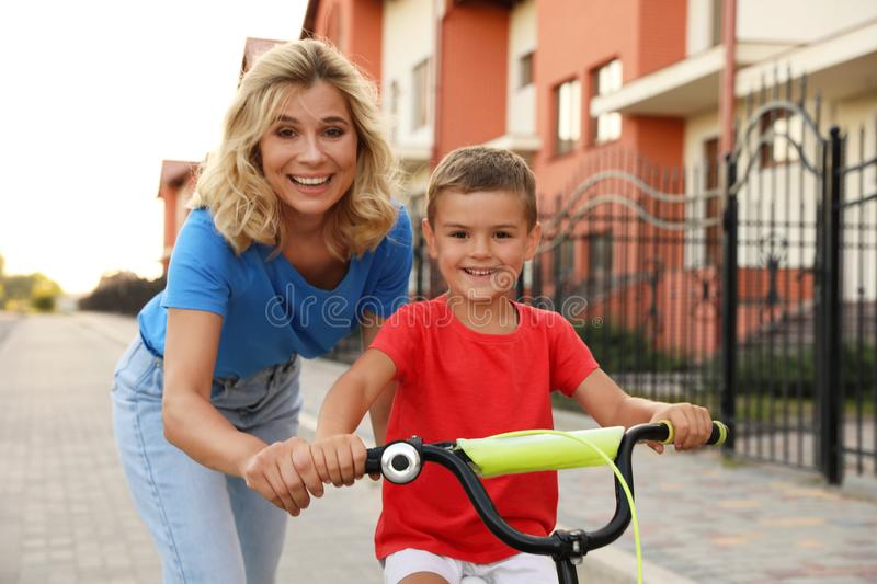 Happy mother teaching her son to ride  in city. Happy mother teaching her son to ride bicycle in city stock photo